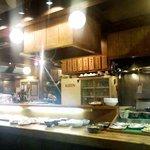 ちょっぷく - 惣菜が並ぶ向こうは炒め物などの料理場。