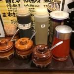 日の出らーめん - 卓上の調味料。前列左から、魚粉、すりおろしニンニク、唐辛子粉、ラー油。後列左から、ガッツ麺のタレ、酢、パウダー胡椒。