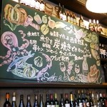 Sante - お店の奥にある黒板とワインボトルの並ぶ棚