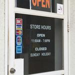 Simply - 店舗外観。入口のドアに営業時間が書いてある。