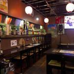 39275850 - 店内は昼でも薄暗い照明。ランチタイムは沖縄音楽を封印、テレビが主役に