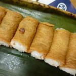 呼きつね - 竹皮の内側には葉らんが その上に一口サイズのお稲荷さんが並んでいます。」