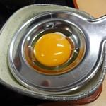 39371270 - 別の椀で出される卵をこの器具の中心部に載せるだけで、黄身と白身を分けることができます。