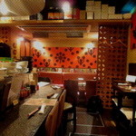 アジアン・ニューヨーク - L字型カウンターと2名掛けのテーブル/店舗奥に4名掛けテーブルとこじんまりとした店内