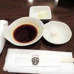 炭火焼ジンギスカン ポッケ - テーブルセットはこんな感じです。       お肉用はタレと塩。       箸休め用にお豆腐の和え物もありました。       紙エプロンも置いてあります。
