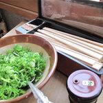 かろのうろん - 卓上です。割箸・小口切りの中ネギ・一味。ネギは入れ放題です。