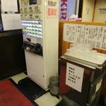 41037929 - 入口脇の券売機とカップ