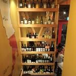 THANK YOU - 階段下のワインボトルがディスプレイされた棚。