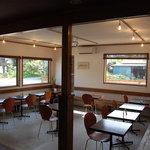 コマチンカフェ - 手作りのベンチが壁面にコの字型に設置。それに向き合うようにテーブルとイス。窓が大きくて明るい。