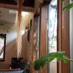 42321074 - 店内の様子。木枠と白壁に鉢植えの緑が映え落ち着いた感じです。