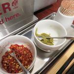 博多もつ鍋前田屋 - 卓上の粗挽き唐辛子と柚子胡椒。チャンポンとラーメンにはニンニクは入ってませんが、リクエスト可能。