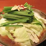 心花 - もつ鍋は醤油味と味噌味とありますが、濃厚な味噌味も良いですが、今回は醤油味で。                             こんな風に盛られた状態で供され、                             「キャベツが煮えたら、お召し上がり下さい。」                             とのことです。