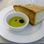 SYM - 表面にローズマリーがトッピングされた自家製パンとオリーブオイル