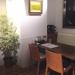 ラ・メーラ - 観葉植物がある窓際のソファ席。絵はヒマワリでした。