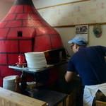 43918769 - オリジナルの窯に生地を入れるオーナー。