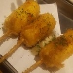 泡盛と串カツのお店 がきんち - チーズ串カツバジルソースがかかってます♪