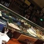 家庭料理 まさき - カウンターのガラスケースに沢山のおばんざい