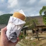 三澤屋茶屋 - 大内宿の景観をバックに「岩魚サンド (540円)」の記念撮影