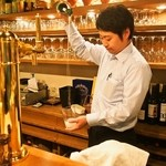 ラコンチャ - スペイン バスク地方の地酒「チャコリ」は高い位置からグラスに注ぐ(写真:店長 高村さん)