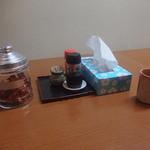 よし村 - 卓上には調味料や、コーヒー用のお菓子?などが置かれています