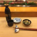 旭寿司 - 熱燗と突出し(ふぐ皮ポン酢)