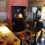 パパチャチャ - 厨房の 真ん中には ピザを焼く石窯が据えられています。
