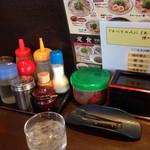 来来亭 - カウンター上の調味料や箸、サービスの梅干し他