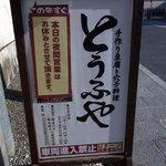とうふや - 通りに出ていたお店の看板です。手作り豆腐と穴子料理 とうふや この先すぐ って書いていますね。