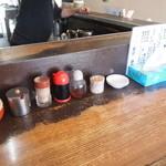 麺屋・高豚 - カウンター周り 辛味噌・ニンニク・コショウ・餃子のタレ・ラー油  ティッシュ完備