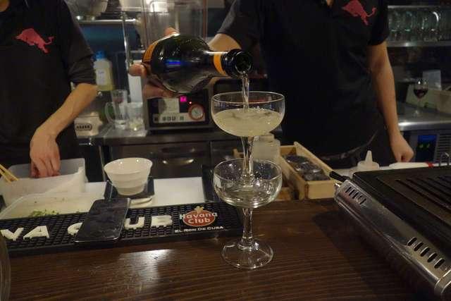 ニクアザブ 六本木店 - その後はこぼれスパークリング600円を注文。ホスト・クラブのシャンパンタワーのようにシャンパングラスを重ねた後に、スパークリングワインを注いでいきます。