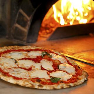 薪窯で焼き上げる薄焼きの熱々ミラノ風ピッツァ