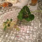 48645531 - 2品目、下がシラウオの揚げ物、上は白身魚、梅、キュウリなどのゼリーをワサビの葉で巻いて食べる
