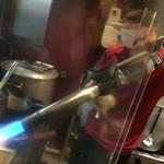 札幌 炎神 - 【2016年02月】スープの入った鍋を火炎放射器みたいなバーナーで炙り始めました。