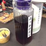 日の出製麺所 - 机の上に出汁と薬味があります。