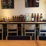 ダイニング・オカノ - 洋酒や焼酎のボトルが並ぶカウンター席
