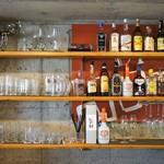 ハングリー - カウンター前の壁は、コンクリート打ちっぱなし、ボトル、グラスが綺麗に並びます