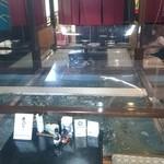 海陽亭 - 生け簀の回りに6人掛け堀座卓のテーブル席が6つあります。