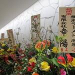 横浜らーめん 源泉 - お祝いの花が並ぶ