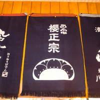 海鮮居酒屋ふじさわ - 店内には日本酒の前掛けやのれんがたくさんあります。