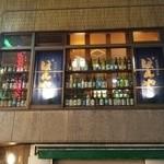 ぼんや - 煙草屋さんの2階、ガラス窓にお酒の瓶がズラーリ