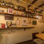 岸町スペインバル クズザンポ - 壁面にはシェリーやワインのボトル(空ですが)や写真など