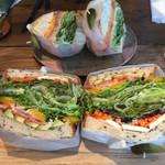 ニーニーサンカフェ - 野菜たっぷりのサンドイッチ(手前)としっかりベーコンが入ったベーグルサンド(奥) 美味しい!大満足!