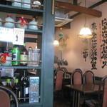 皇庭餃子房 - 店内 テーブル席。壁には、イラストと共に漢詩