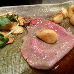 シャカ - 牛肉の薄切り。ニンニクを丸ごと包んで食べる。