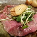 シャカ - 牛肉の薄切り。ニンニクチップを包んで食べる