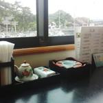 51049331 - 店内と窓の外に見える海と水祖(みおや)神社