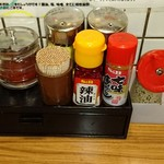 Yokohamaramenouka - 卓上調味料。左からおろしニンニク、豆板醤、酢、醤油、ラー油、七味唐辛子、スリゴマ、ブラックペッパー、おろし生姜。下の黒い箱は割りばしが入った引き出し。