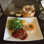 アスタルエゴ - 青森県産津軽鶏と彩り野菜のトマト煮1,300円(税込)と遊び心を感じるセットのグラスワイン(白)