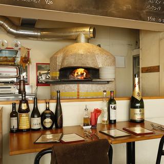 窯でのピッツァの焼き上げを目の前で見る事が出来るカウンター席