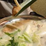 完全個室居酒屋 天凛 新横浜駅前店 - 地鶏つみれ付京出汁豆乳鍋の地鶏つみれを入れているところ(料理9品コース)